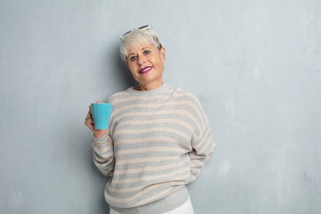 Mulher fresca sênior com um café contra a parede do cimento do grunge.