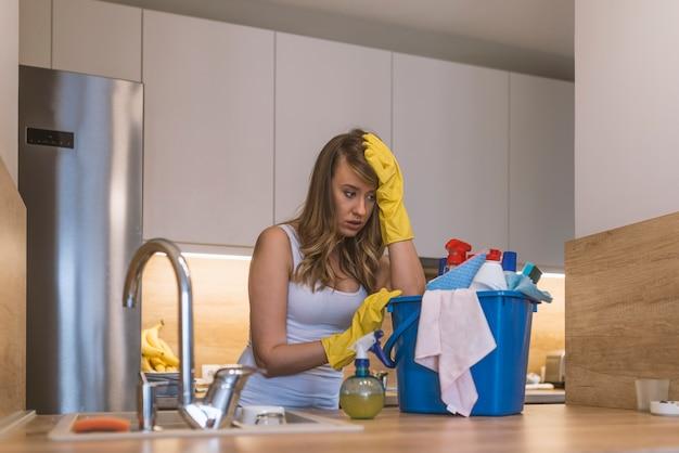 Mulher frustrada com luvas de borracha segurando cesta com material de limpeza na frente da kitc