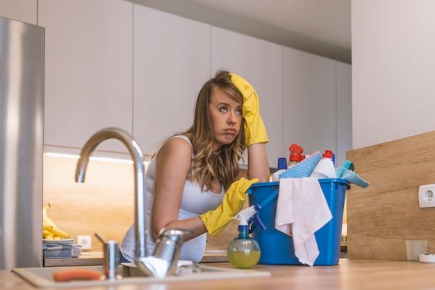 Mulher frustrada com luvas de borracha segurando cesta com material de limpeza na frente do kit