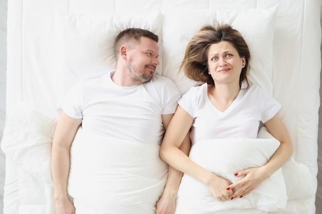 Mulher frustrada deitada na cama com um homem sorridente, conceito de vida familiar íntima