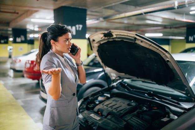 Mulher frustrada e angustiada tem uma falha de carro em um local público em uma garagem subterrânea. ela está pedindo ajuda.