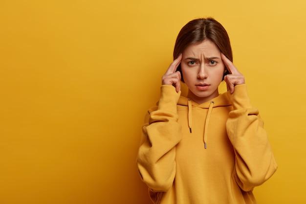 Mulher frustrada e descontente toca as têmporas com o dedo indicador, concentra-se em algo e pensa em uma ideia, tenta tomar uma decisão séria, sofre de dor de cabeça