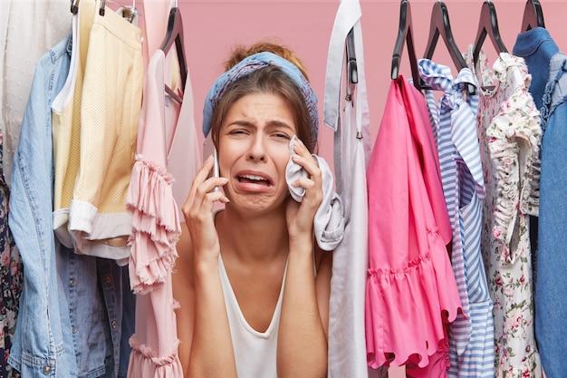 Mulher frustrada em pé perto de prateleira cheia de roupas, conversando com sua amiga por telefone inteligente, reclamando que ela não tem nada para vestir, tendo expressão triste. roupas, conceito de moda