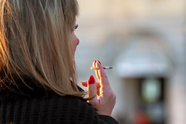 Mulher fuma um cigarro na rua. mau hábito.