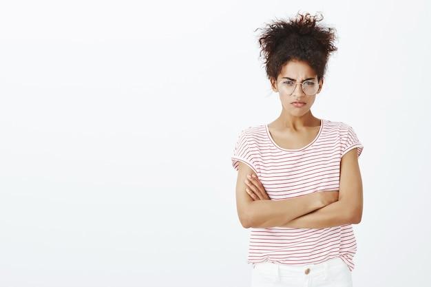 Mulher furiosa com penteado afro posando no estúdio
