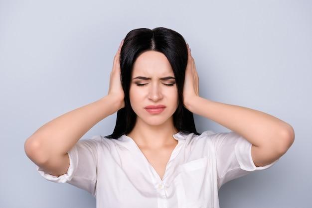 Mulher furiosa com um grande problema tocando a cabeça e cobrindo as orelhas. ela não quer ouvir ninguém agora