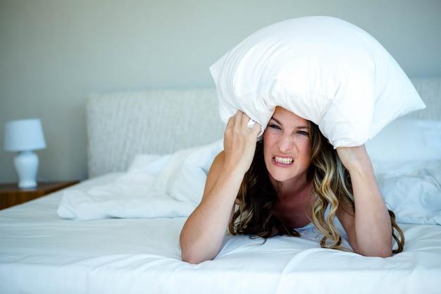 Mulher furiosa, deitada em uma cama com um travesseiro na cabeça