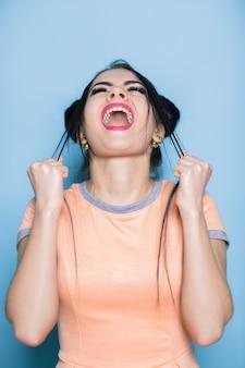 Mulher furiosa e frustrada gritando no azul