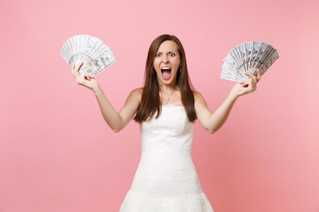 Mulher furiosa e irritada em um vestido branco gritando, segurando um pacote de muitos dólares, dinheiro em espécie