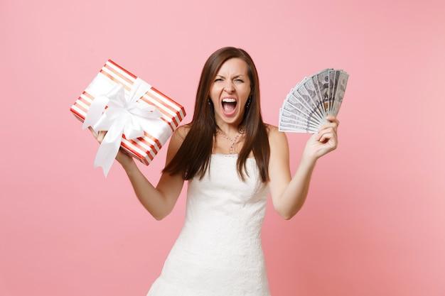 Mulher furiosa em um vestido branco gritando segurando um pacote de muitos dólares, dinheiro em espécie, caixa vermelha com presente, presente