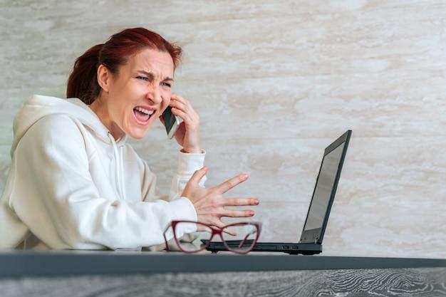 Mulher furiosa freelancer furiosa gritando com seu telefone