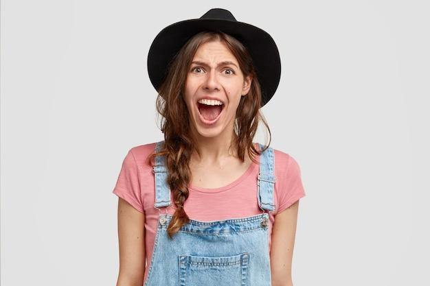 Mulher furiosa irritada grita de raiva, fica descontente com os resultados do trabalho em seu jardim, expressa emoções negativas, usa roupas casuais do campo