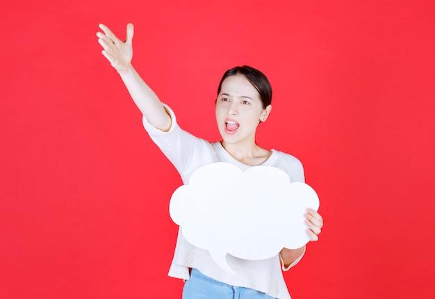 Mulher furiosa segurando um balão de fala em forma de nuvem