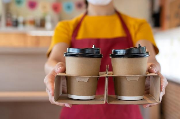 Mulher garçonete amigável usando máscara facial de proteção esperando para servir uma xícara de café quente ao cliente no café, restaurante, serviço de mente, novo normal, conceito de entrega de comida e bebida