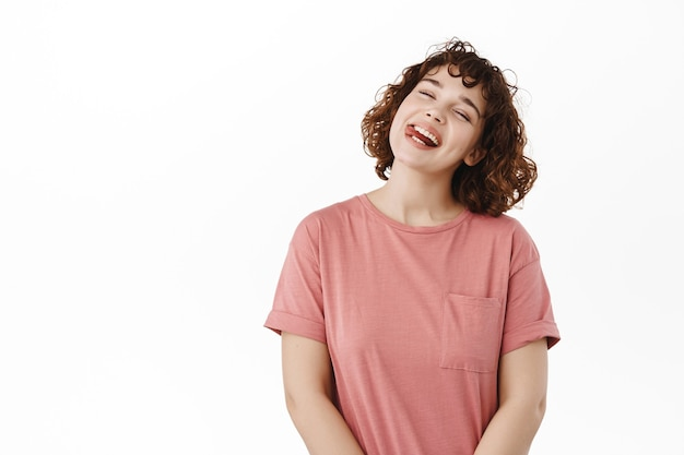 Mulher, garota mostra sorrisos e risos de língua, inclina a cabeça despreocupada, aproveite as férias de verão, positivo em branco.