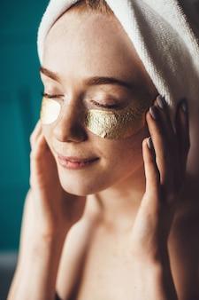 Mulher gengibre com sardas aplicando tapa-olhos de hidrogel enquanto usava uma toalha na cabeça