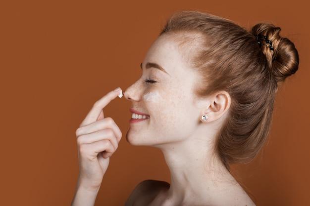 Mulher gengibre com sardas aplicando um creme no rosto e sorrindo com os ombros nus em uma parede marrom com espaço livre