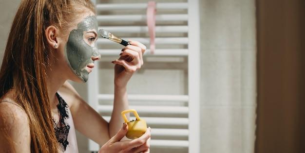 Mulher gengibre em frente ao espelho aplicando uma máscara facial usando ferramentas especiais