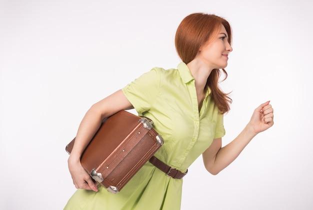 Mulher gengibre segurando uma mala marrom velha