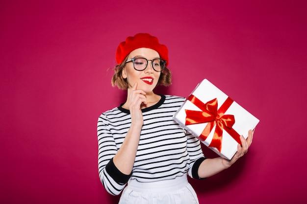 Mulher gengibre sorridente intrigada em óculos, segurando e olhando para a caixa de presente sobre rosa