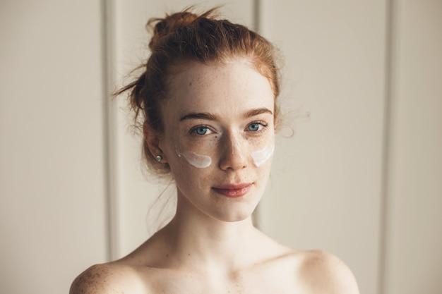 Mulher gengibre usando tapa-olhos de hidrogel olhando para a câmera com os ombros nus