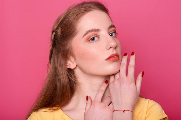 Mulher gentil com maquiagem brilhante, cabelos lisos com tom vermelho