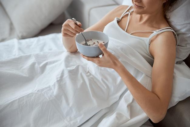 Mulher gentil encostada no travesseiro enquanto vai tomar seu café da manhã