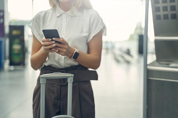 Mulher gentil segurando o telefone com as duas mãos enquanto procura a passagem online antes do voo