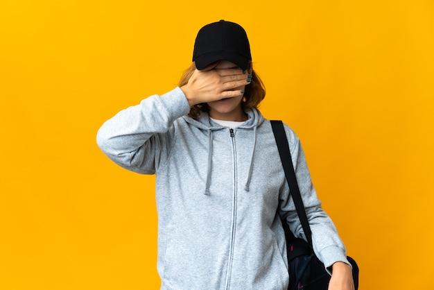 Mulher georgiana do esporte jovem com bolsa de esporte sobre fundo isolado, cobrindo os olhos com as mãos. não quero ver nada