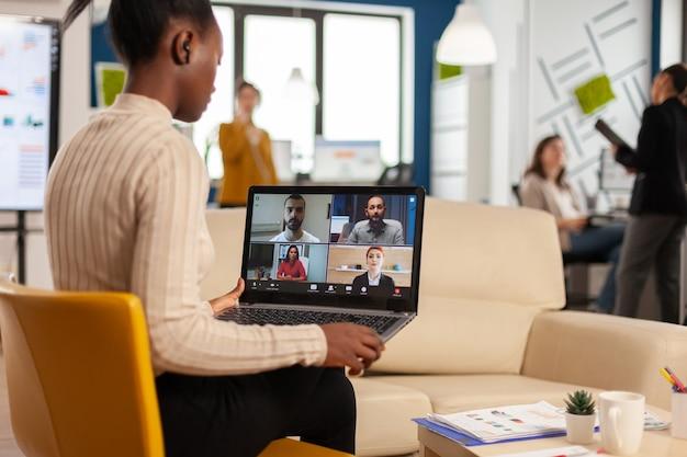 Mulher gerente africana discutindo com colegas remotos usando videochamada segurando laptop sentado no sofá em um escritório moderno