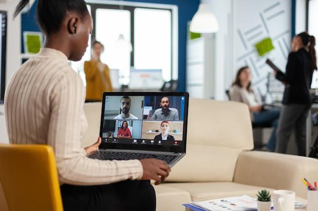 Mulher gerente discutindo com colegas remotos usando videochamada segurando laptop sentado no sofá em um escritório moderno
