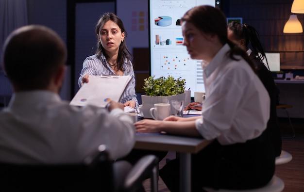 Mulher gerente executiva explicando estatísticas de gerenciamento trabalhando horas extras na estratégia da empresa na sala de reuniões do escritório