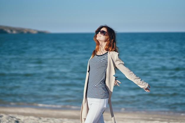 Mulher gesticulando com as mãos acima da cabeça na praia perto do mar, céu de verão