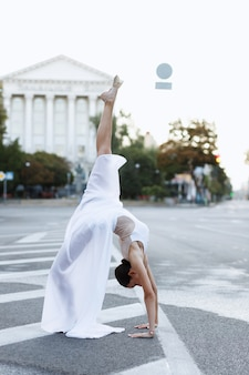 Mulher ginasta na cidade com lindo vestido