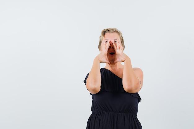 Mulher glamorosa chamando alguém em voz alta, de blusa preta e parecendo enérgica. vista frontal. espaço para texto