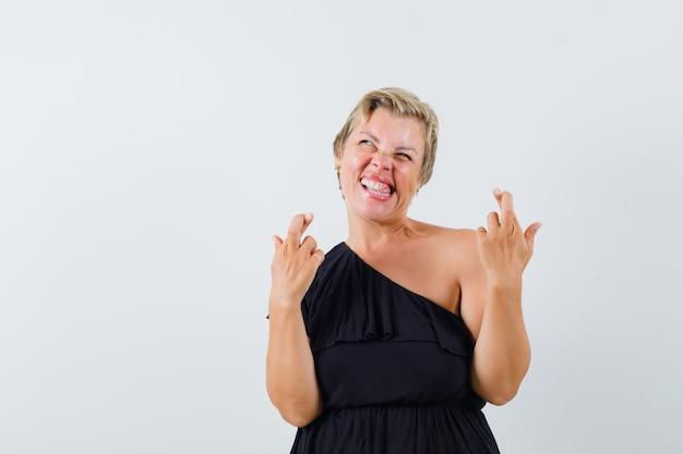 Mulher glamorosa com os dedos cruzados enquanto ria de blusa preta e parecendo louca