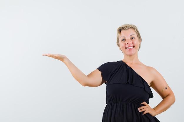 Mulher glamorosa espalhando a mão com a palma aberta de lado na blusa preta e parecendo feliz. vista frontal.