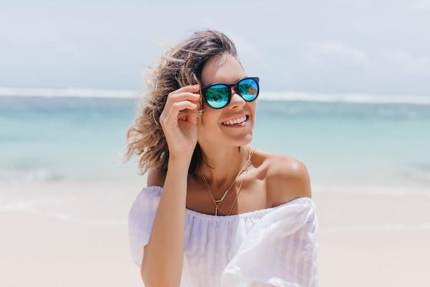 Mulher glamorosa no vestido branco, aproveitando o verão no resort. retrato de uma senhora bronzeada deslumbrante em óculos de sol em pé perto do mar.