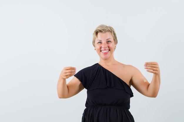 Mulher glamorosa posando como se estivesse segurando algo na mão em uma blusa preta e parecendo alegre