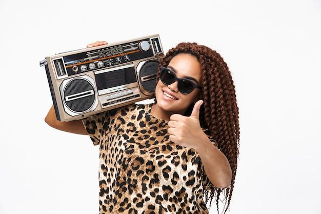 Mulher glamorosa sorrindo e segurando uma caixa de som vintage com fita cassete no ombro, isolada contra uma parede branca