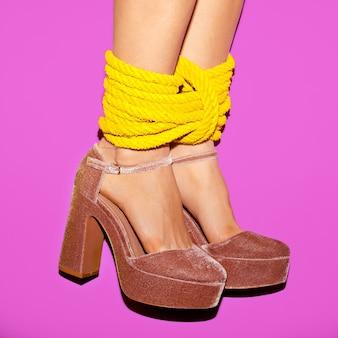 Mulher glamourosa de salto alto amarrado com uma corda. hora de brincar