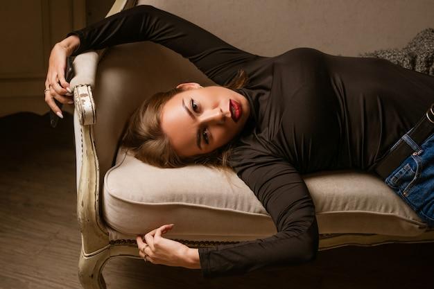 Mulher glamourosa elegante com uma maquiagem brilhante e lábios vermelhos está deitada no sofá