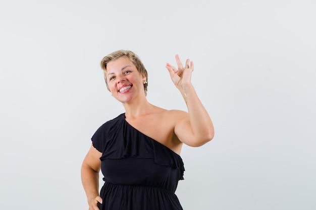 Mulher glamourosa em blusa preta mostrando um gesto de ok e parecendo alegre