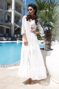 Mulher glamourosa no vestido claro branco, verão, quente, brades, em pé perto das palmeiras, senhora sexy, praia, areia, mar, piscina, vestido ondulando,