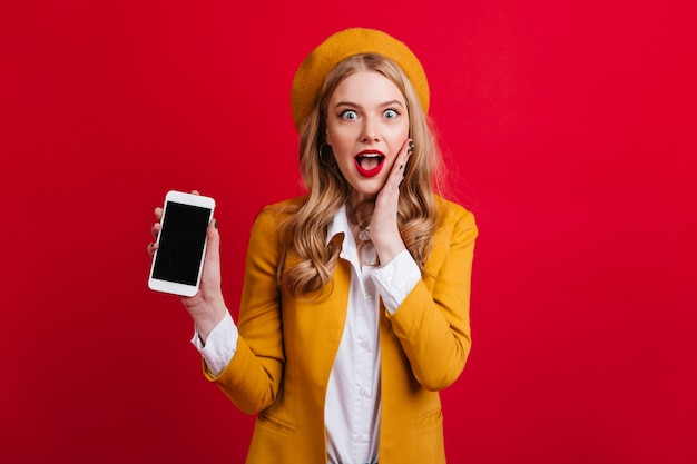 Mulher glamourosa surpresa segurando smartphone com tela em branco na parede vermelha. loira atraente em boina amarela posando com dispositivo digital