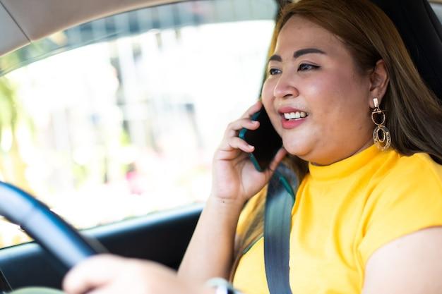 Mulher gorda aaian no carro, falando no celular enquanto dirige.