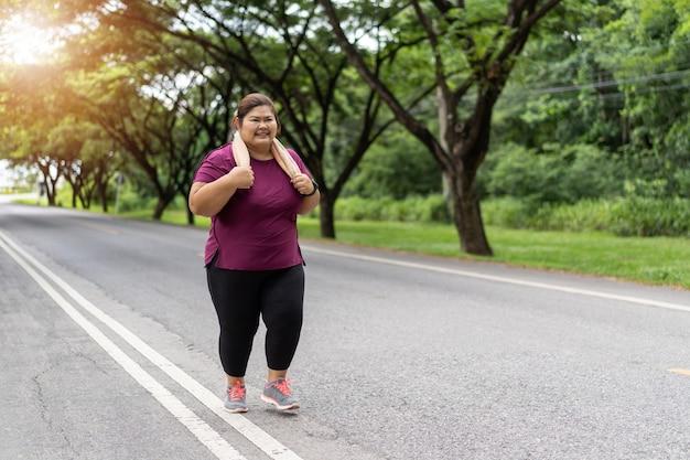 Mulher gorda asiática correndo, faz exercícios para o conceito de ideia de perda de peso.