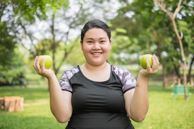 Mulher gorda asiática da aptidão nova que realiza na maçã verde das mãos no parque natural
