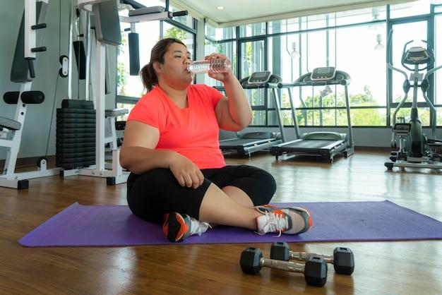 Mulher gorda asiática luta com excesso de peso na academia, fazendo exercícios pesados de fitness