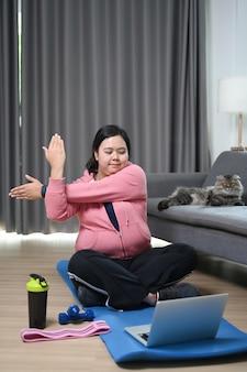 Mulher gorda assistindo o vídeo de treinamento de fitness no laptop e esticando os braços em casa.